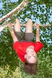 Tonårig pojke som hänger från ett träd i en sommarträdgård Arkivfoton
