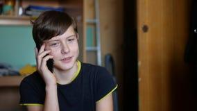 Tonårig pojke som inomhus talar på telefonsmartphonen arkivbilder