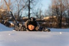 Tonårig pojke som ligger i snön royaltyfri bild