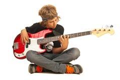Tonårig pojke som spelar bas- quitar Arkivfoto