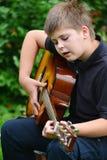 Tonårig pojke som spelar gitarren som är utomhus- i en sommar Royaltyfri Fotografi
