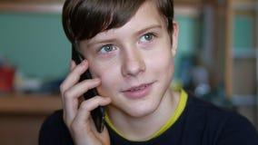 Tonårig pojke som talar på den inomhus smartphonen för telefon royaltyfria foton
