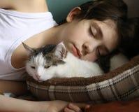 Tonårig pojkesömn med katten arkivfoto