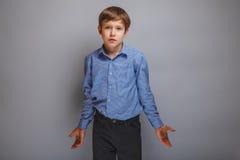 Tonårig pojkespridning hans armar i misstro på grå färger Fotografering för Bildbyråer