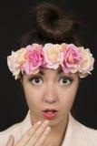 Tonårig skönhet som bär en blom- krona med ett förvånat uttryck Arkivfoto