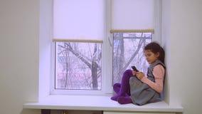 Tonårig spela rengöringsduk för flicka direktanslutet leken för smartphone- och hundsammanträde på husdjur för fönsterfönsterbräd lager videofilmer