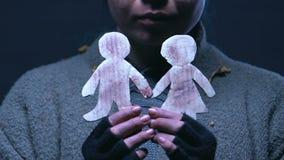 Tonårig tiggare som kramar små pappers- män och att drömma av föräldrar och bättre liv arkivfilmer