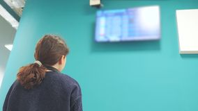 Tonårig turist- ung flicka hålla ögonen på flygschemat av hennes avvikelse flygplatsen se informationsbrädelivsstil stock video