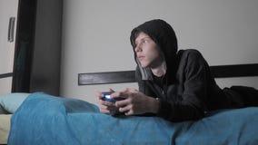 Tonårig ung pojke och med huva tröja för styrspakmancybersport som absorberas i online-videospellivsstil pojketonåring i stock video