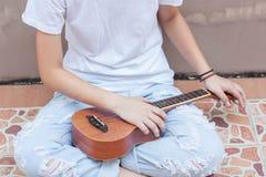 Tonåriga asiatiska kvinnor med ukulelet i hennes fria tid royaltyfria foton