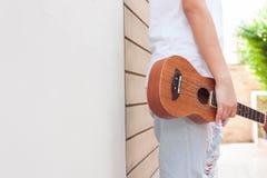 Tonåriga asiatiska kvinnor med ukulelet i hennes fria tid arkivbilder