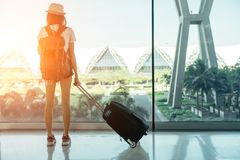 Tonåriga asiatiska kvinnor som står med bagage eller resväskan på fönstret royaltyfria foton