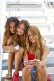 Tonåriga bästa vänflickor i rad med smartphonen royaltyfria bilder