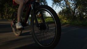 Tonåriga ben för Closeup och cykelhjul som rider på vägen lager videofilmer
