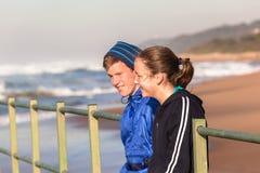 Tonåriga för Tid för pojkeflickasamtal vågor strand Arkivbilder