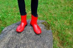 Tonåriga flickaben som bär röda gummistöveler arkivbilder