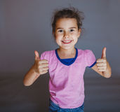 Tonåriga flickashower gör en gest ja på grå bakgrund Arkivfoton