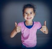 Tonåriga flickashower gör en gest ja på grå bakgrund Royaltyfria Foton