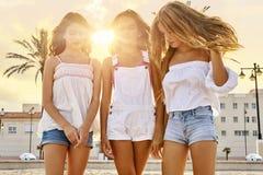 Tonåriga flickor för bästa vän som är roliga i en strandsolnedgång arkivbilder