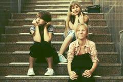 Tonåriga flickor för lyckligt mode som sitter på moment Fotografering för Bildbyråer