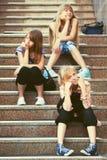 Tonåriga flickor för lyckligt mode som sitter på moment royaltyfria foton