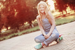 Tonåriga flickor med med skateboarden i sommar parkerar Royaltyfria Bilder