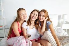 Tonåriga flickor med selfiepinnen som hemma fotograferar arkivbild
