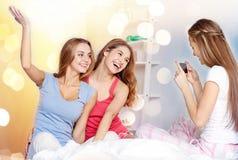 Tonåriga flickor med smartphonen som hemma tar bilden arkivfoton