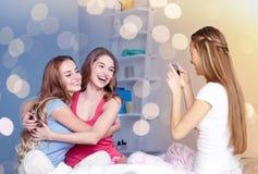 Tonåriga flickor med smartphonen som hemma tar bilden royaltyfria foton