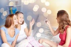 Tonåriga flickor med smartphonen som hemma tar bilden royaltyfria bilder