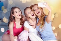 Tonåriga flickor med smartphonen som hemma tar selfie arkivbilder