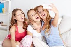 Tonåriga flickor med smartphonen som hemma tar selfie arkivfoton