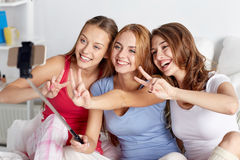 Tonåriga flickor med smartphonen som hemma tar selfie arkivbild