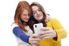 Tonåriga flickor med telefonen Royaltyfria Bilder