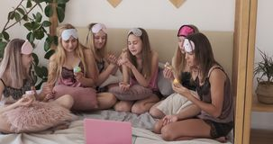 Tonåriga flickor som dansar och äter muffin, medan hålla ögonen på film på bärbara datorn stock video