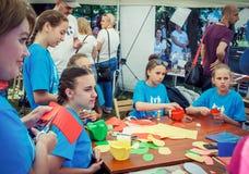 Tonåriga flickor som deltar, i framställning av det färgrika seminariet för pappers- blommor Royaltyfri Fotografi