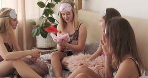 Tonåriga flickor som har gyckel som skriver med vingpennan i bok under pajamapartiet stock video