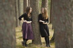 Tonåriga flickor som står i en skog nära ett träd som till varandra talar Natur Royaltyfri Foto