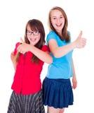 Tonåriga flickor som står upp och visar tummar Arkivbild