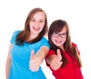 Tonåriga flickor som visar upp tummar Arkivbild