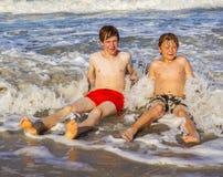 Tonåriga pojkar har gyckel under sjösidaferie Arkivfoton