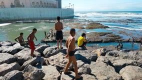 Tonåriga pojkar som hoppar i havet i Casablanca Marocko Royaltyfri Bild