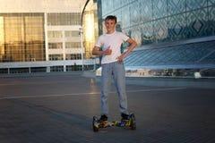 Tonåriga ritter på en elektrisk sparkcykel, med ett leende och realitetsinnesrörelser arkivfoto