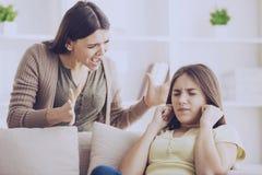 Tonåriga stängda öron med händer, medan mamman skriker royaltyfri foto