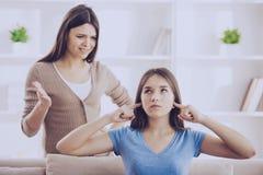 Tonåriga stängda öron med händer, medan mamman skriker arkivfoton