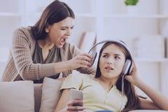 Tonåriga stängda öron med headphonen, medan mamman skriker royaltyfri fotografi