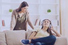 Tonåriga stängda öron med headphonen, medan mamman skriker arkivfoto