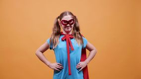 Tonårigt förställde som en superhero framme av en orange bakgrund lager videofilmer