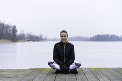 Tonårigt flickasammanträde för härlig svensk caucasian kondition på den wood bron som är utomhus- i vinterlandskap royaltyfri bild
