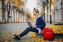 Tonårigt flickasammanträde för nätt hipster på en trottoar på höststadsgatan och arbetebärbar datordatoren Använda för skolflicka royaltyfri fotografi